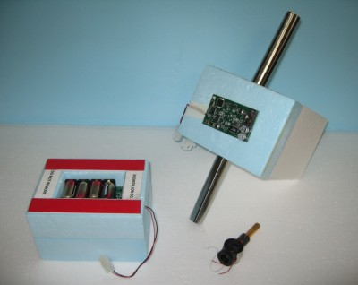 Similar to a standard radiosonde, the frost point hygrometer is a digitally-controlled instrument attached to a weather balloon. As it rises through the air, atmospheric data collected by the sensor is recorded on the ground. This photo shows the computer chips, battery pack, and connector that make up the instrument package.