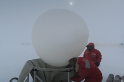 Heath Powers, Los Alamos National Laboratory, and Dan Lubin, AWARE lead scientist, prepare a weather balloon at WAIS Divide Ice Camp. Image courtesy of Dan Lubin.