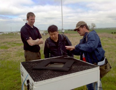 Daniel Hartsock and Dr. Kyungjeen Park look on as Pat Dowell describes the operation of a disdrometer at the SGP site. A sensor under the instrument's 'hood' measures rain rate and drop size distribution.