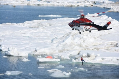 A helicopter crew lowers rescue swimmer into the Arctic Ocean during a joint exercise with the Coast Guard and other private firms to assess using manned and unmanned aerial systems for search and rescue near Oliktok Point, Alaska, July 13, 2015. The test took place in DOE airspace recently approved for research by the FAA (Coast Guard photo by Petty Officer 2nd Class Grant Devuyst).