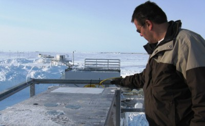 Walter Brower, Barrow site facilities manager for ARM, cleans the sampling surface in preparation for the next snow storm. Visible in the background is the site's automated weather balloon launcher.