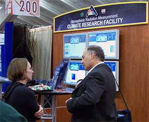 Jennifer Delamere talks about her research experiences using the ARM Climate Research Facility with an interested researcher at the fall meeting of the American Geophysical Union.