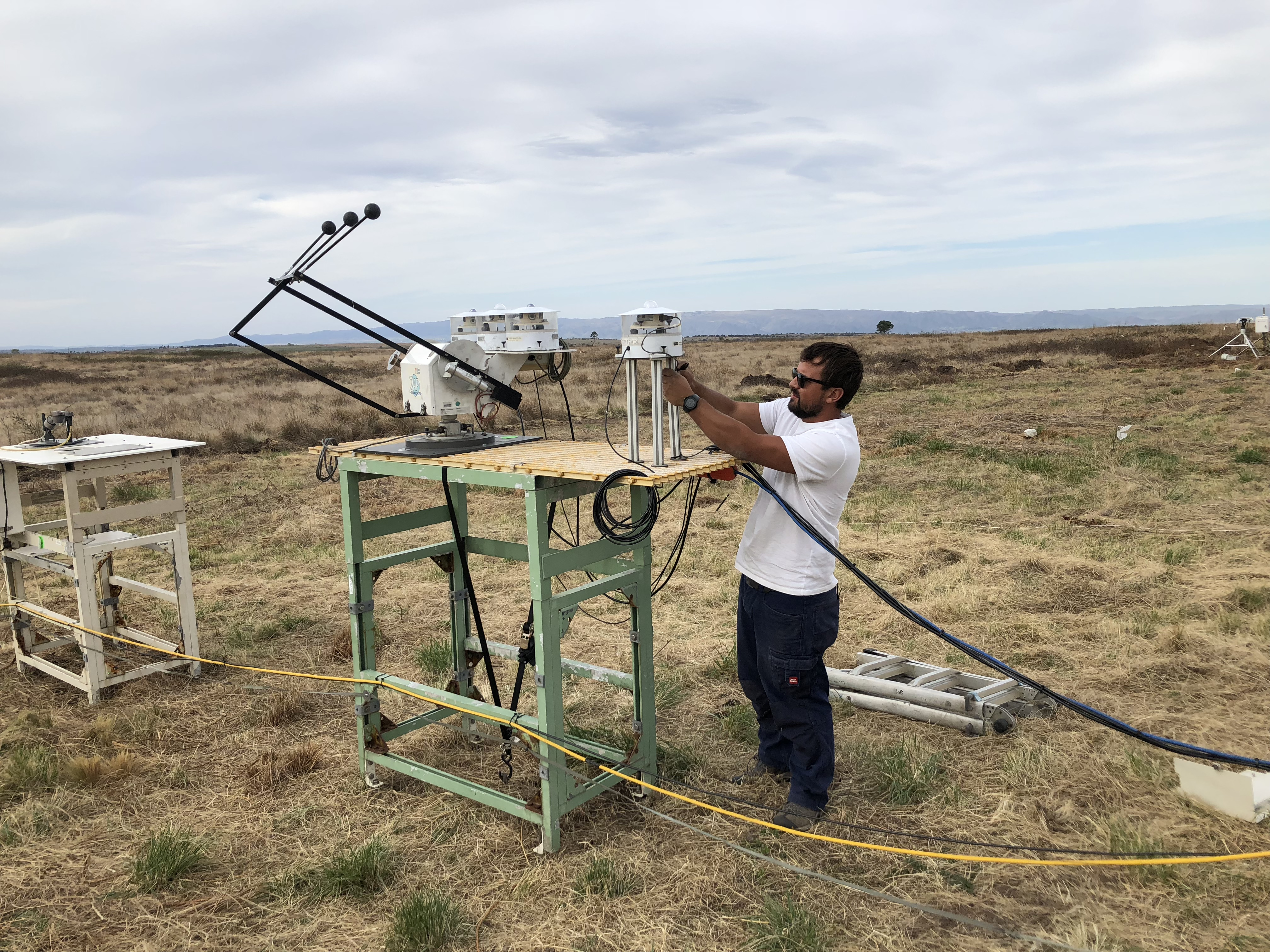 Technician works on ARM sky radiometers on stand for downwelling radiation in Argentina