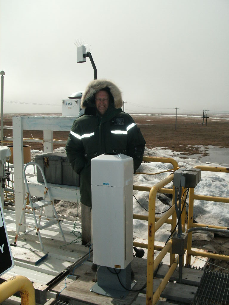 In Barrow, Alaska, mentor Victor Morris poses with a ceilometer he oversees, an instrument used to measure cloud-base height and other climate-critical factors.