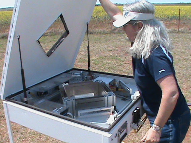 In the field at Southern Great Plains, Argonne-based disdrometer mentor Mary Jane Bartholomew looks under the hood of a 2DVD disdrometer.